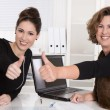 Two business woman working in a team - smiling and thumbs up. — Stock Photo