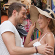 Attractive couple on shopping tour: woman wants to buy a summer — Stock Photo
