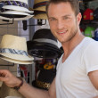 Portrait of handsome man wants to buy a summer hat. — Stock Photo