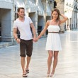 Attractive couple walking through the city on their summer holid — Stock Photo