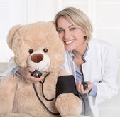 Gelukkig arts voor kinderen met een teddybeer. — Stockfoto
