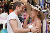 Attractive couple on shopping tour: woman wants to buy a summer — Stok fotoğraf