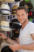 Portrait of handsome man wants to buy a summer hat. — Foto Stock