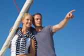Attractive couple on sailing boat: man pointing with forefinger — Stock Photo