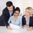 Teamwork between three business people at desk at office. — Stock Photo #41100871