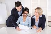 在办公室的办公桌的三个商业人士之间的团队精神. — 图库照片