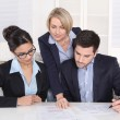 Stock Photo: Teamwork between three business people at desk at office.