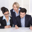 Teamwork between three business people at desk at office. — Stockfoto