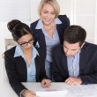 Teamwork between three business people at desk at office. — Stock Photo #41185799