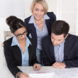 Teamwork between three business people at desk at office. — Stock Photo