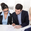 Young couple has consultation with consultant at desk at office. — Stock Photo