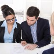 Young couple has consultation with consultant at desk at office. — Stock Photo #41186191