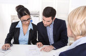 Young couple has consultation with consultant at desk at office. — Foto de Stock