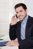 Handsome smiling businessman on telephone in his office. — Stok fotoğraf