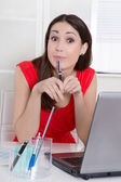 Pensive attractive trainee sitting at desk at office. — Stockfoto