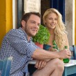 Happy young couple in summer holidays sitting in a outdoor resta — Stock Photo #41337859
