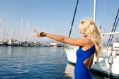 Young woman on sailing holidays pointing with her forefinger. — Stock Photo