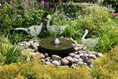 Close up from a fountain with stones and plants at a garden. — Stock Photo