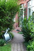 Close up from a paved path with house facade and watering can. — Stock Photo