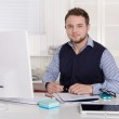 Young handsome successful accountant at desk at office. — Stock Photo #41727369