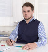 Young handsome bookkeeper working with graphs at desk. — Stock Photo