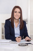 在办公室伏案工作的年轻迷人微笑女商人 — 图库照片