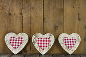 Checked hearts of wood on wooden background. — Foto de Stock