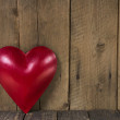 Red metal heart on wooden background — Stock Photo