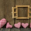 Checked hearts of fabric and wooden window frame. — Stock Photo