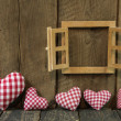 Checked hearts of fabric and wooden window frame. — Stock Photo #41910597