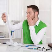 Pensive controller working with calculating machine at desk. — Stock Photo
