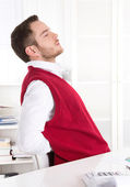 Young handsome clerk with backache at office. — Stock Photo