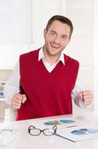 Happy bookkeeper with fists at desk at office. — Stock Photo