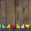 Colorful hearts on a wooden background for a greeting card. — Stockfoto