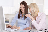 Fun at office: two smiling female coworkers in front of the comp — Stock Photo