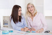 Teamwork at office with two young attractive businesswomen. — Stock Photo