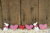 Country style easter wooden background with red checked hearts. — Stock Photo