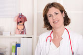 Portrait of pretty smiling physician with stethoscope at treatme — Stockfoto