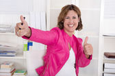 Portrait of successful attractive businesswoman with thumbs up a — Stockfoto