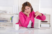 Bad mood: woman in the office with thumb down — Stockfoto