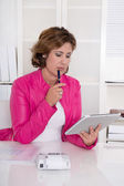 Brunette considering businesswoman in pink jacket at desk.  — Stockfoto