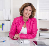 Smiling business woman sitting satisfied at desk. — Stock Photo