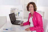 Smiling secretary sitting satisfied at desk at office. — Stockfoto