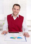 Satisfied accountant working with graphs sitting at desk. — Stockfoto