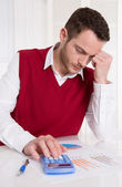 Young considering accountant with pocket calculator at desk. — Photo