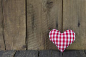 Red white checked sewed heart on a wooden background. — Stock Photo