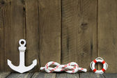 Nautical decoration with anchor and knot on a wooden background. — Stock Photo