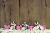 Red checked hearts on wooden background for easter. — Photo
