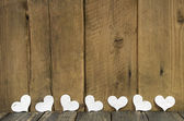 White hearts on a wooden old rustic background in shabby style. — Stock Photo