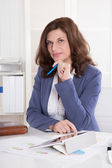 Portrait: Successful older business woman sitting in her office. — Stockfoto